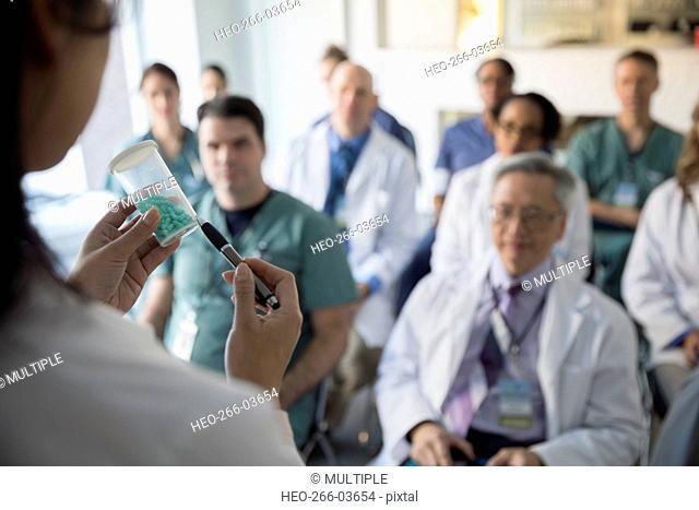 Doctor leading seminar explaining prescription medication to audience