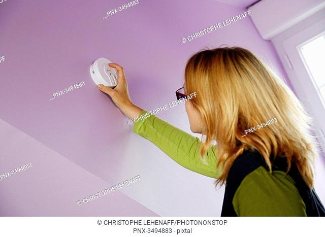 France, around Paris, 42 year old woman installing a smoke detector