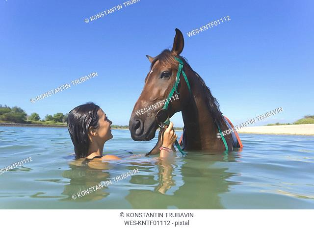 Indonesia, Bali, Woman with horse in the water