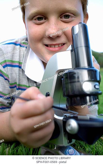 Boy using a light microscope