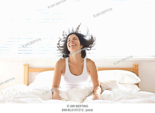 Smiling Hispanic woman sitting in bed