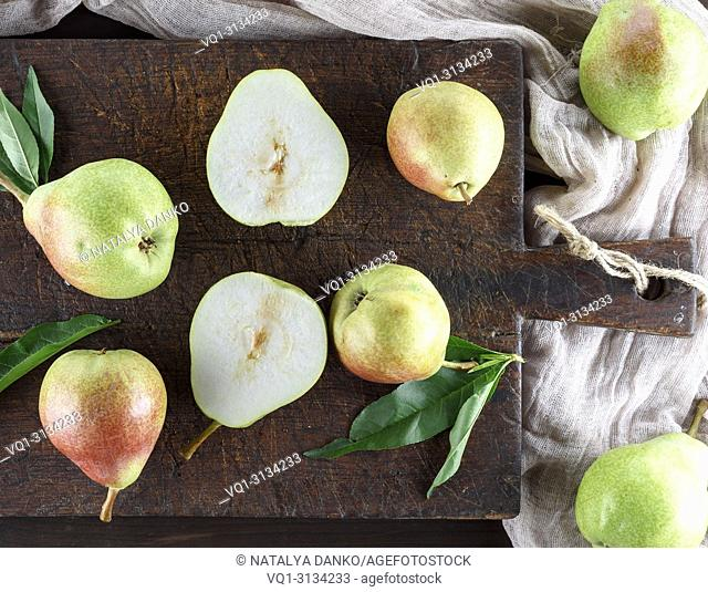 ripe green pears on a brown wooden board, top view