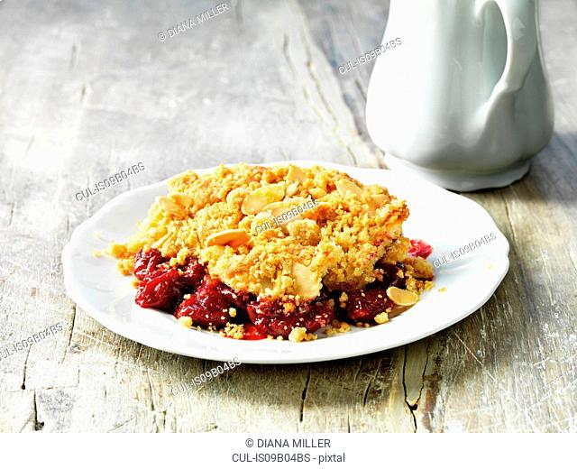 Sour cherry and almond crumble pudding on white plate, white washed rustic wooden table