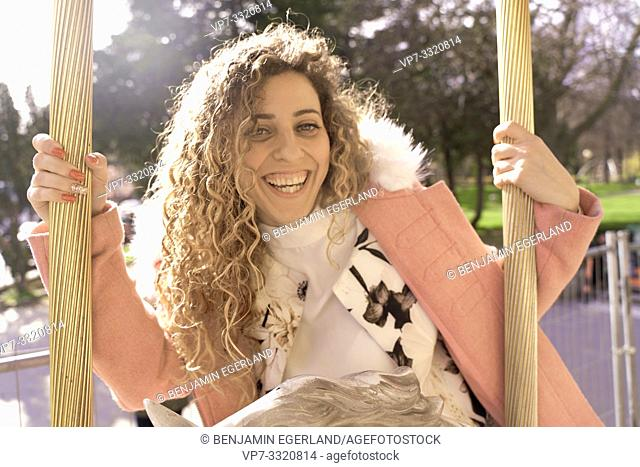 woman at amusement Carousel, in Paris, France