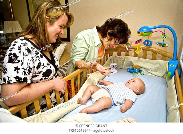 Babysitting her 6-month-old grandson, a grandmother in Laguna Niguel, California, interacts with the child as a relative watches