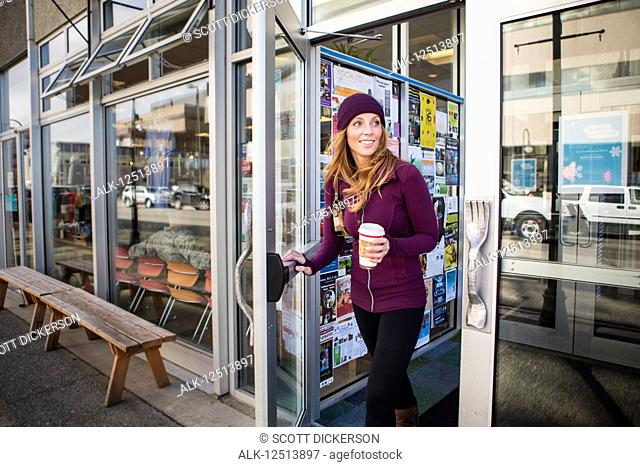 Young woman leaving a cafe with a drink in downtown Anchorage, South-central Alaska; Anchorage, Alaska, United States of America