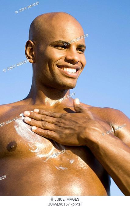 African man applying sunscreen