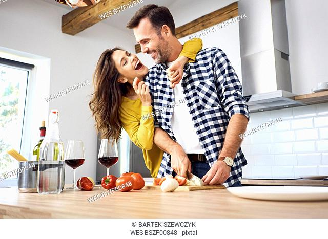 Affectionate couple in kitchen, preparing spaghetti toghether