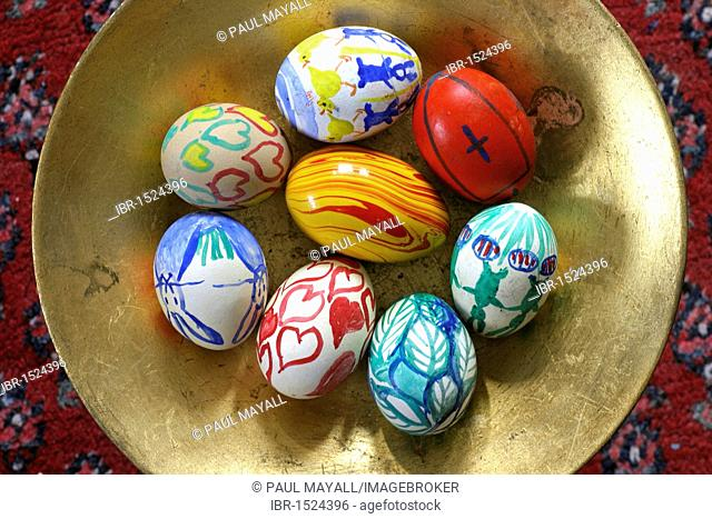 Hand-painted Easter eggs in a gold coloured bowl