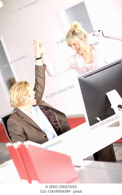 businesswoman and businessman high five