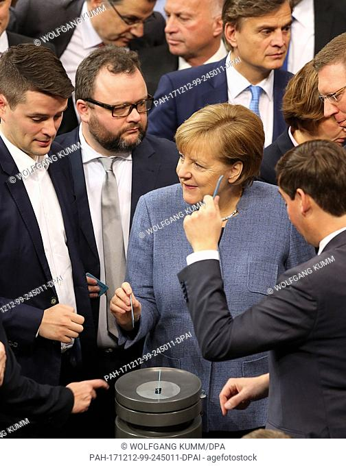 German chancellor Angela Merkel (Christian Democratic Union - CDU) casts her vote regarding the Anti-IS campaign among other parliamentarians during a meeting...