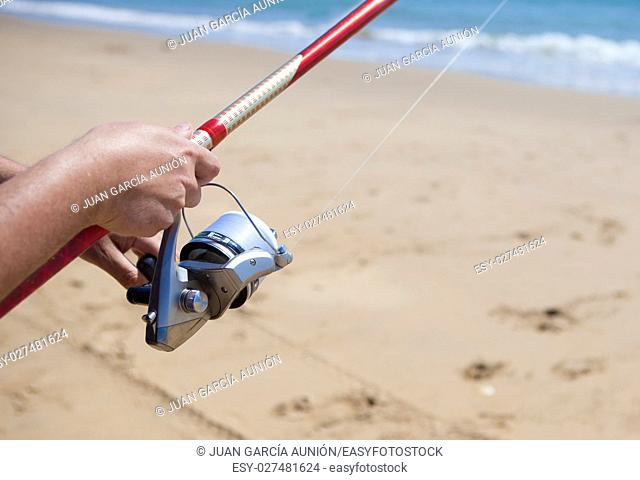 Folding the fishing line. Sea angling sport at the beach
