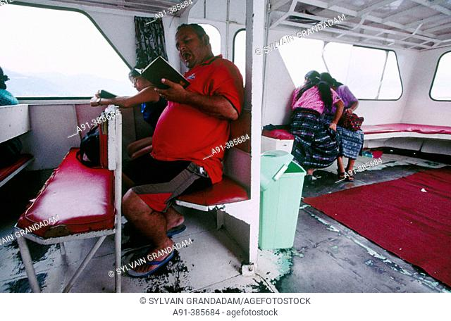 Local passenger reading a thriller onboard a ferry crossing the lake Atitlan. Guatemala