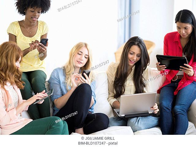 Women using technology on sofa