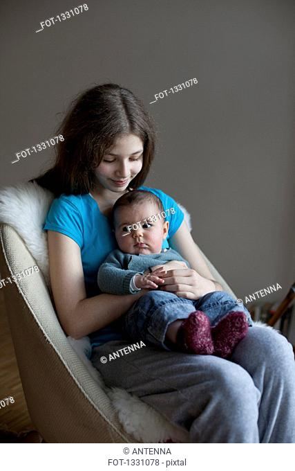 Smiling sister looking at baby girl on chair