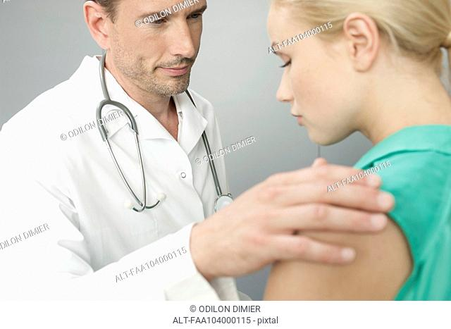 Doctor comforting upset patient