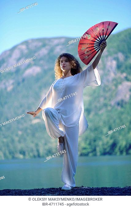 Young woman practicing Tai Chi with a red fan in a Crane, one-leg standing stance, at at mountain lake shore in the nature