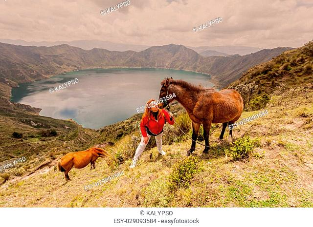 Blonde Woman With Two Horses Near The Edge Of The Mountain, Quilotoa Lake In The Background, Ecuador, South America