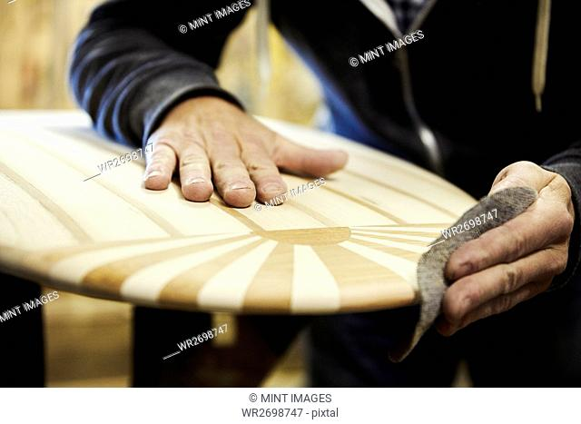 Man in a workshop sanding the edge of a wooden surfboard with a surface pattern of inlaid wood