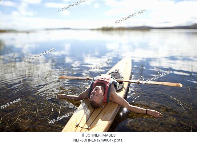 Young man sleeping in canoe, Norrbotten, Sweden