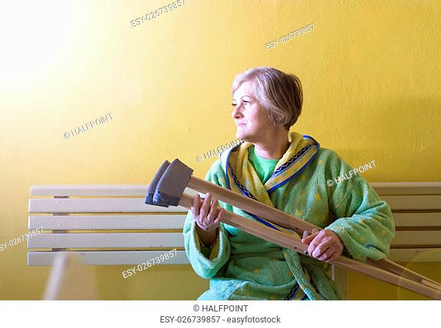 05caba02d0 Senior woman injured sitting in the hallway of hospital holding crutches