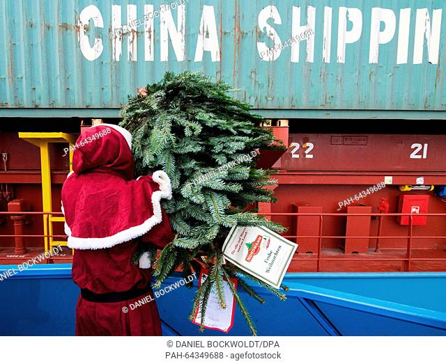 A man dressed as Santa throws a Christmas tree onto a container ship in the port of Hamburg, Germany, 10 December 2015. For the 19th time