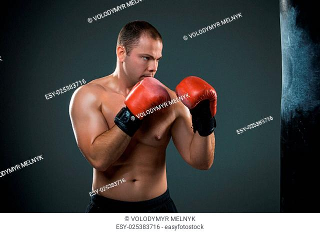 Young boxer in red gloves boxing over black background