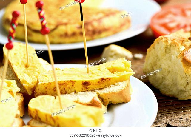 closeup of a plate with tortilla de patatas, spanish omelet, served as tapas on sliced bread and a toothpick through it, on a table