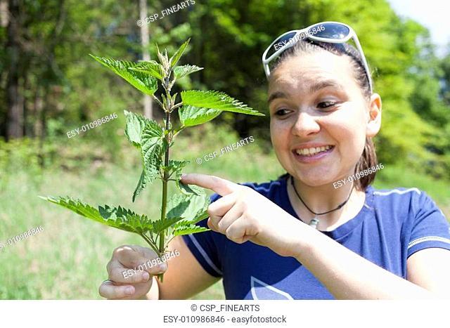 Girl touching stinging nettle leave