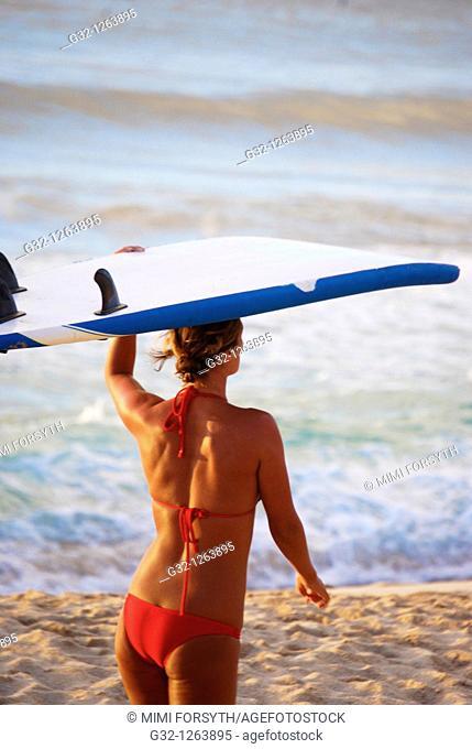 Girl carries surfboard on beach, Hawaii, USA