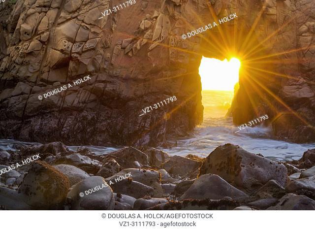 Rays of sunlight shine through iconic Pfeiffer Beach Arch, Big Sur, California, USA