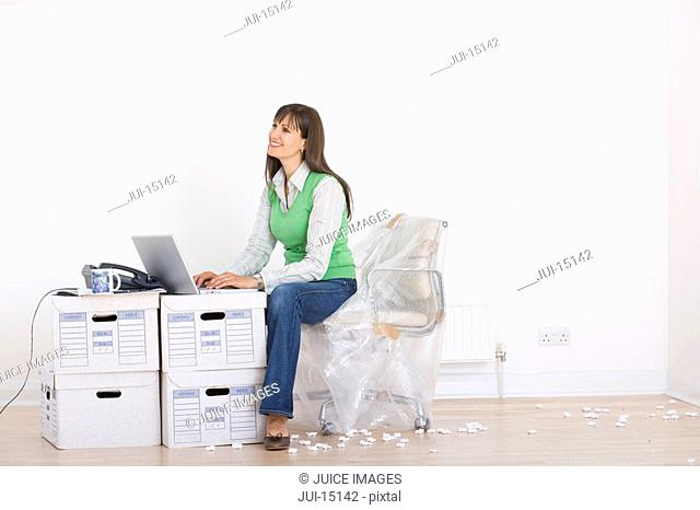 Woman working amidst boxes