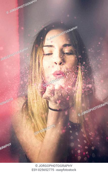 Creative pink abstract portrait on the face of a beautiful woman blowing a burst of magic glitter at valentine's day party celebration