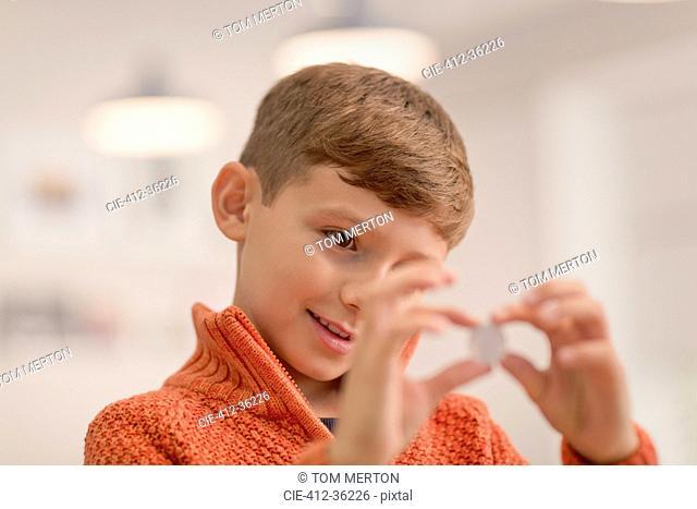 Curious boy holding coin