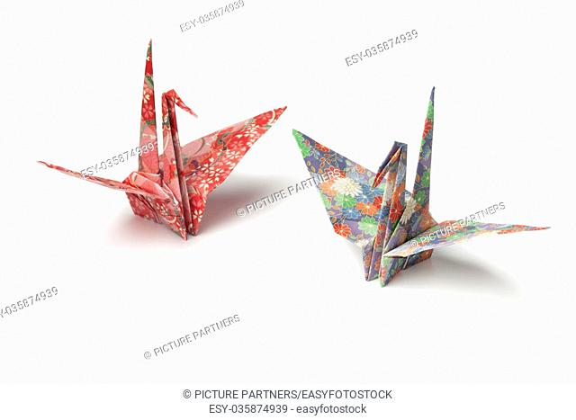Two origami paper crane birds on white background