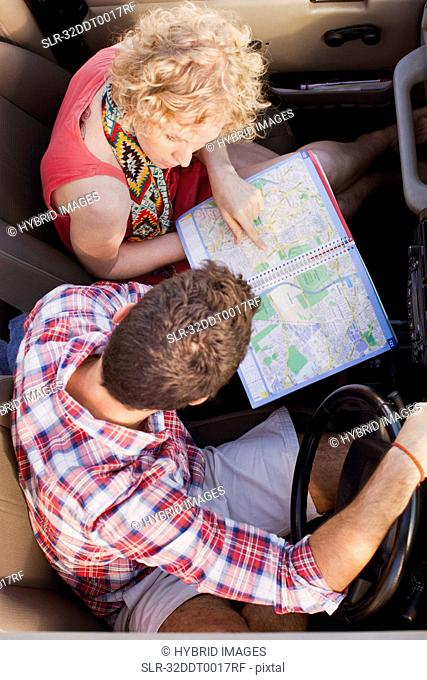 Couple examining map in jeep