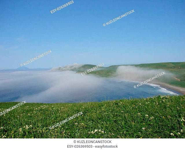 The island Urup, Russia, on July, 5th, 2007, steep coast, from passage Fruze approaches a fog