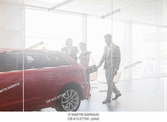 Car salesman showing new car to customers in car dealership showroom