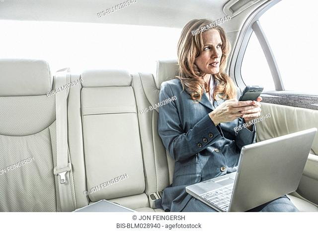 Businesswoman working in backseat of car