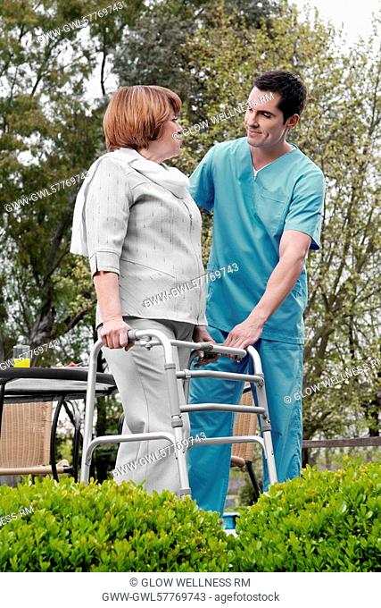 Health worker assisting a disabled woman in a rehabilitation center