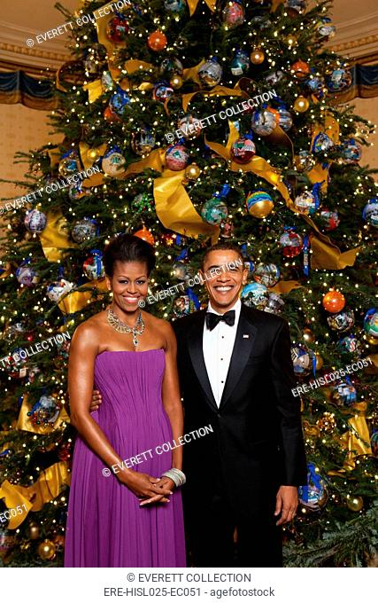 President and Michelle Obama pose in front of the Official White House Christmas Tree Dec. 6 2009. Michelle wears a purple pleated chiffon dress with a corset...