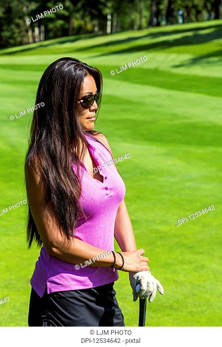 A female golfer stands on the green grass of a golf course watching in the distance while holding her golf ball and club; Edmonton, Alberta, Canada