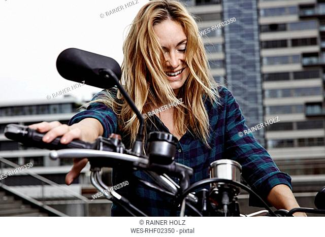 Laughing young woman on motorcycle