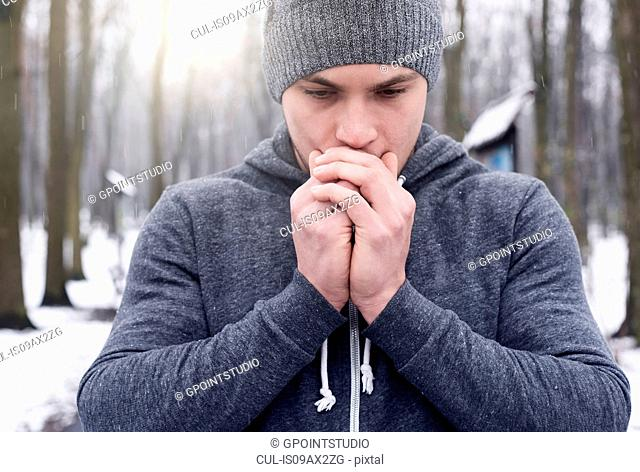 Young man breathing on hands, in snowy forest