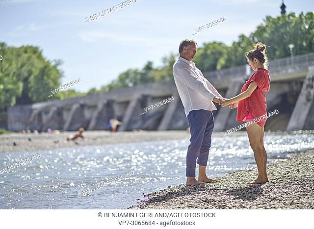 Couple, pregnancy, exercising, age difference, togetherness, love. At river Isar, Munich, Germany