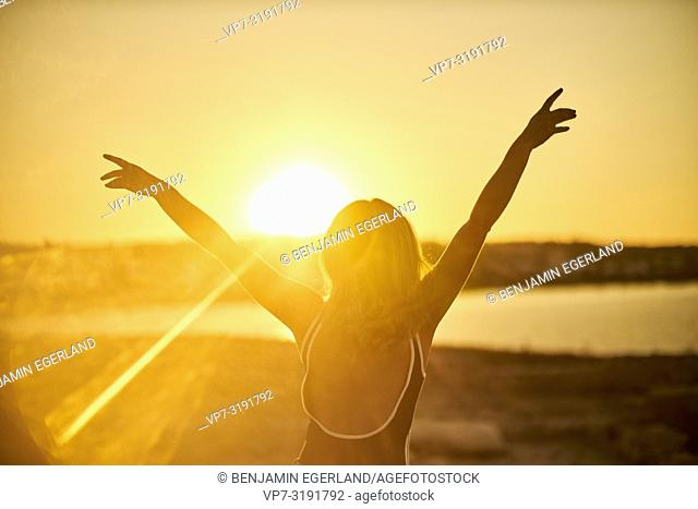 woman stretching arms, seaside, sunflare, sunset, freedom, holiday, vacations, joy