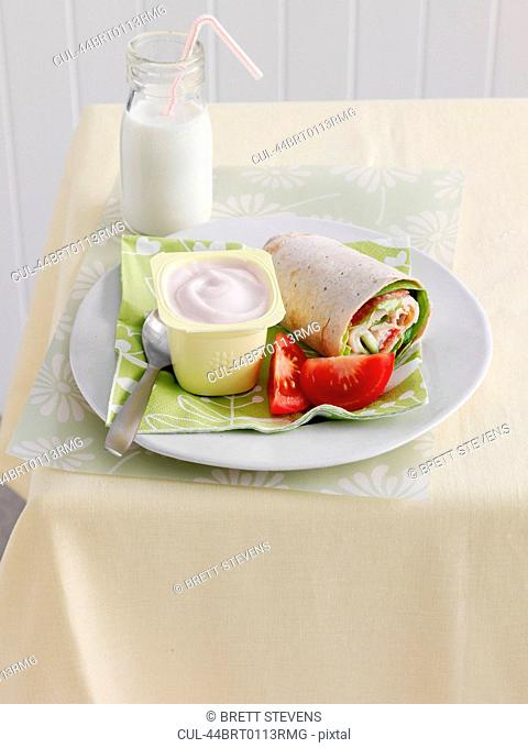 Plate of wrap, yogurt and tomatoes