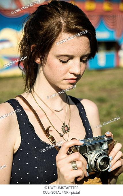 Young woman photographing on SLR camera at funfair
