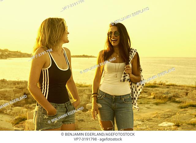 two women at ancient ruins, friends, seaside, hanging out, together, holiday, in Chersonissos, Crete, Greece