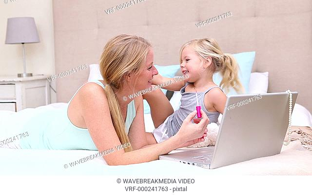 Mother and daughter lying on bed using laptop at home in bedroom